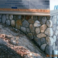 Custom stonework fit around sloped foundation