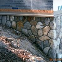 Custom stonework fit around sloped foundation