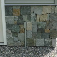 Stones laid on facade of residential garage.