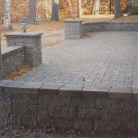Brick patio with a stone wall
