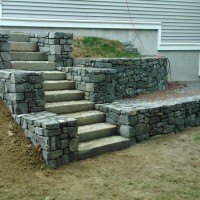 Outdoor stone steps with retainer wall